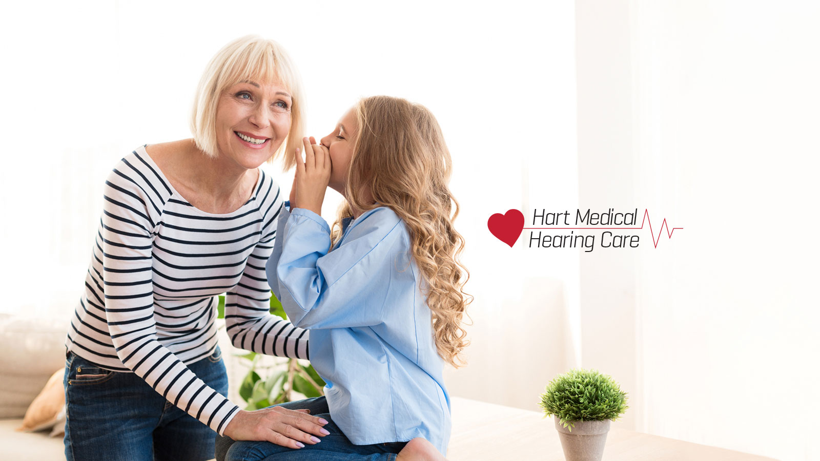 young girl speaking in older woman's ear with hart medical logo